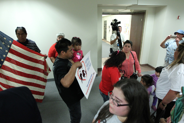 Immigration activists deliver a letter and sign to Attorney General Adam Laxalt's office at the Grant Sawyer Building, 555 E Washington Ave., in Las Vegas Tuesday, May 19, 2015. Activists and thei ...
