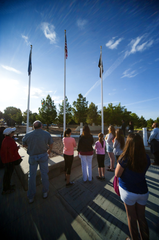 Flag placement volunteers sing the National Anthem before adorning 25,896 graves with American flags at the Southern Nevada Memorial Veterans Cemetery in Boulder City on Saturday, May 23, 2015. Ov ...