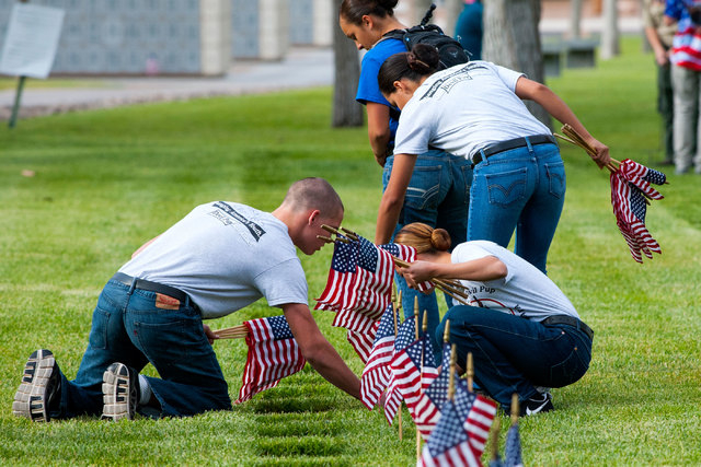 Members of the Southern Nevada Devil Pups adorn some of the 25,896 graves with American flags at the Southern Nevada Memorial Veterans Cemetery in Boulder City on Saturday, May 23, 2015. Over 35 o ...
