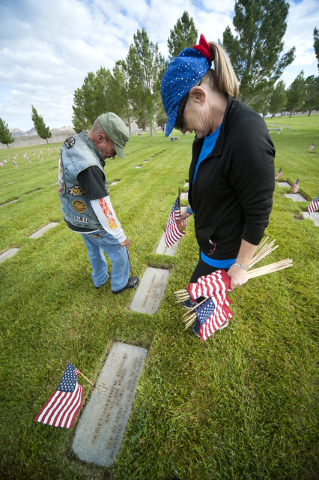 """""""Sarge,"""" a member of the Patriot Guard, and Linda O'Leary adorn one of 25,896 graves with an American flag at the Southern Nevada Memorial Veterans Cemetery in Boulder City on Saturday, May 23, 20 ..."""