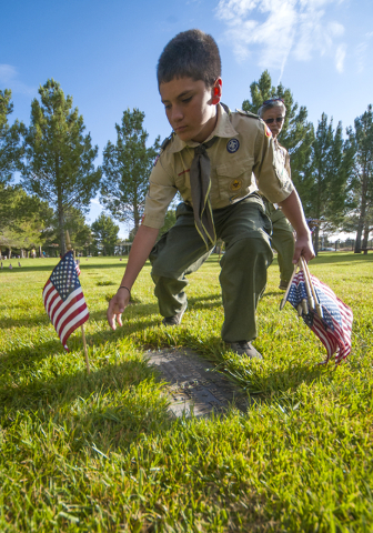 D'Angelo Quartucci, a member of Henderson Troop 903, Boy Scouts of America, positions an American flag on one of 25,896 graves at the Southern Nevada Memorial Veterans Cemetery in Boulder City on  ...