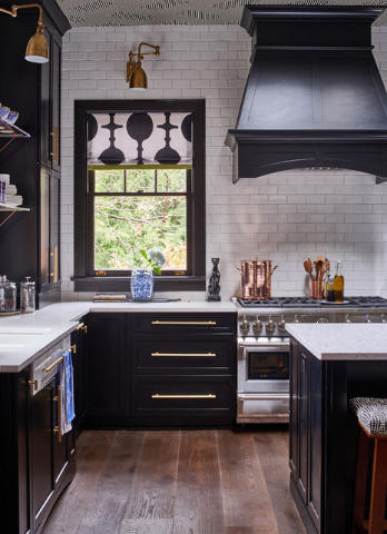 Photo by Dustin Peck Appliances are stainless steel but the drawer pull are gold in this black-and-white kitchen by Lisa Mende Design.