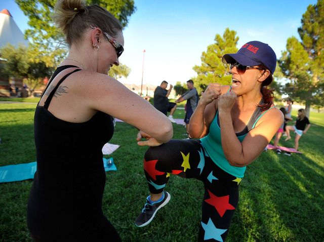 Laura Ritter, left, and boot camp organizer Nicole Sharp spar with each other during their workout session at the Mission Hills free boot camp at Mission Hills Park in Henderson, June 23. (David B ...