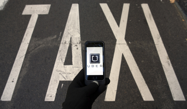 The logo of car-sharing service app Uber on a smartphone over a reserved lane for taxis in a street is seen in this photo illustration taken in Madrid on December 10, 2014. A Madrid judge has orde ...