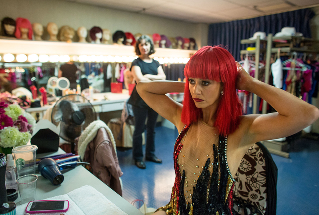"Lisa Cannon adjusts her wig before performing in ""Crazy Girls"" as wardrobe supervisor Holly McKinnis looks on Friday, Feb. 14, 2014 at the Riviera Hotel and Casino. McKinnis is a theatre ..."