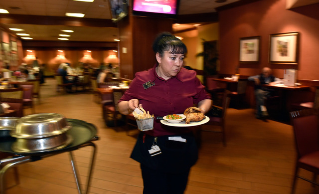Server Irma Diaz delivers a chicken plate and basket of fries to a customer at Cafe Cortez in the El Cortez May 4, 2015. (David Becker/View)