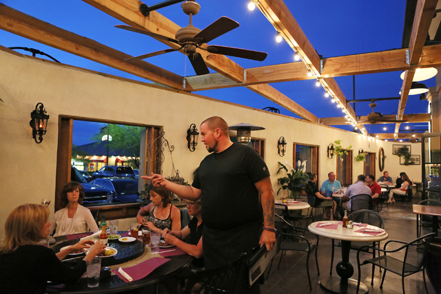 Adam Curling, standing, serves a table in the courtyard at Lola's Summerlin location May 1, 2015. (Ronda Churchill/View)