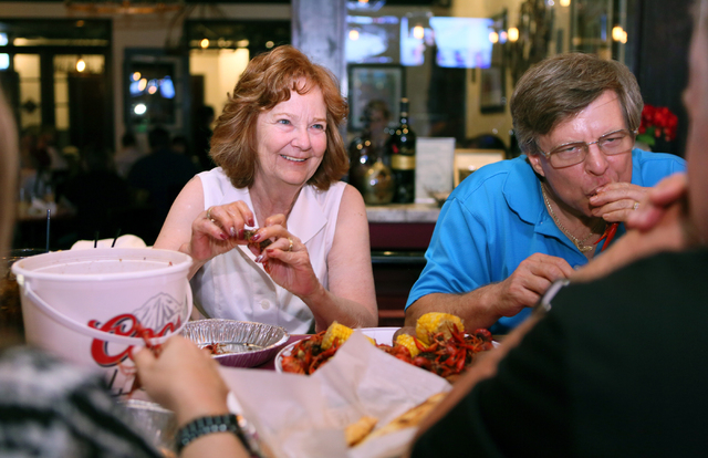 Guests Kris Melancon, left, and Ralph Melancon eat steamed crawfish at Lola's Summerlin location May 1, 2015. (Ronda Churchill/View)