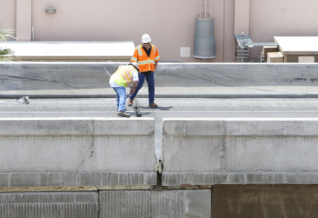 Officials from the Nevada Department of Transportation investigate possible damage on the ramp from southbound U.S. Route 95 to southbound Interstate 15 on Friday, May 22, 2015. A 4.8-magnitude ea ...