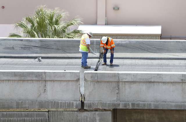 Officials from the Nevada Department of Transportation investigate possible damage on the ramp from southbound U.S. Route 95 to southbound Interstate 15 on Friday, May 22, 2015.  (Bizuayehu Tesfay ...