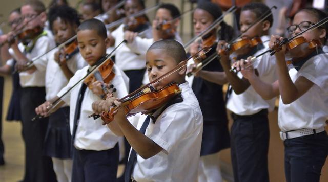 Rainbow Dreams Academy fourth-grader Ayiden Tyler, center, plays violin during a recital at the Historic Fifth Street School. (Bill Hughes/View)