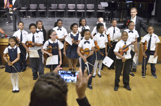 DeShana Allen, foreground, takes a picture of Patrick Clark, Rainbow Dreams Academy violin program coordinator, back right, and some of his students after they participated in a recital April 11 a ...