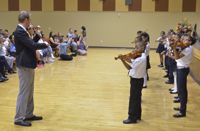 """Patrick Clark, violin program coordinator at the Rainbow Dreams Academy, leads students in """"Twinkle Variations in D"""" during a recital at the Historic Fifth Street School. (Bill Hughes/View)"""