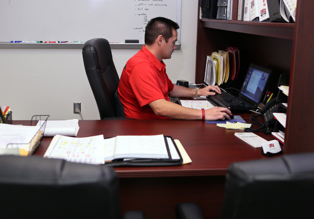 Jimmy Morimoto, director of player personnel and assistant recruiting coordinator for UNLV football, works in his office at UNLV Friday, May 15, 2015, in Las Vegas. Morimoto, who is originally fro ...