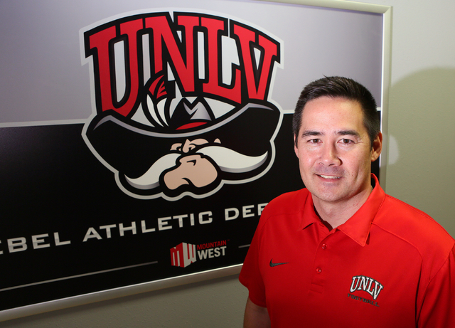 Jimmy Morimoto, director of player personnel and assistant recruiting coordinator for UNLV football, stands near a poster at UNLV's Lied Athletic Complex Friday, May 15, 2015, in Las Vegas. Morimo ...