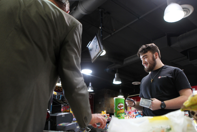 U.S. Rep. Cresent Hardy, R-Nev., left, scans the items of customer Adam Harrison at the Green Valley Grocery, 5225 Camino Al Norte, in North Las Vegas with store manager Emily Dages on Wednesday,  ...
