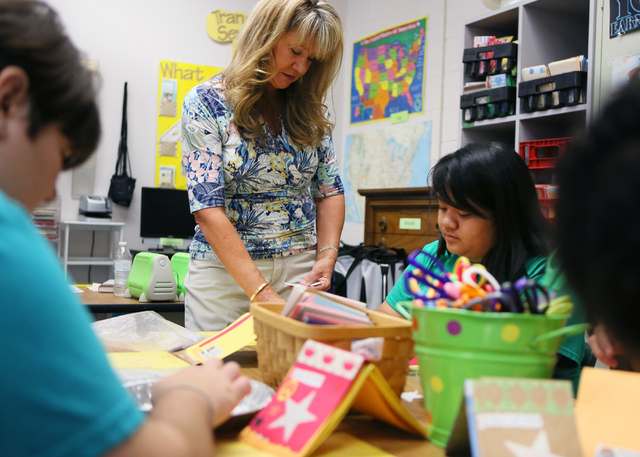 Lisa Cipriano, center, works with her students Peyton Petrillo, left, and Kealani Buenaventura to make greeting cards in a special education class at Silverado High School Wednesday, May 13, 2015, ...