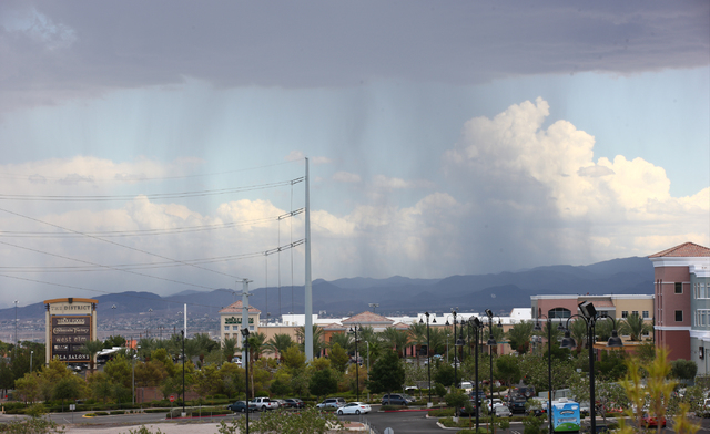 Storm clouds loom above as rain comes down in parts of Henderson as seen from The District at Green Valley Ranch looking east on Wednesday, Aug. 20, 2014. (Chase Stevens/Las Vegas Review-Journal)