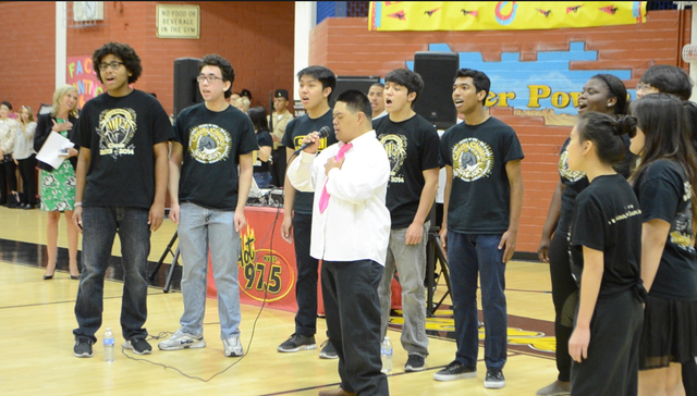 Calvin Sierra, a senior in Clark High School's special education program, performs the national anthem alongside the choir at a community hero-themed dance for special education students. (Ginge ...
