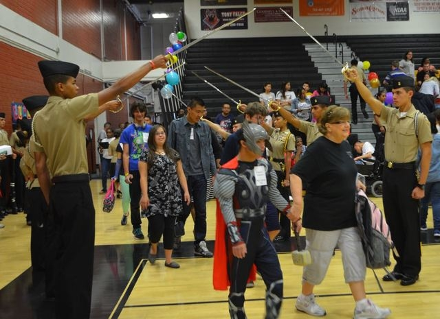 Students enter the Clark High School gym May 5 through a military honor saber arch at a community hero-themed dance for special education students at Clark High School, 4291 Pennwood Ave. (Ginger  ...
