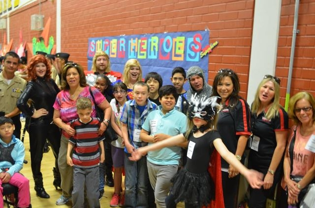 Students pose for a photo at the entrance to a community hero-themed dance for special education students at Clark High School. (Ginger Meurer/Special to View)