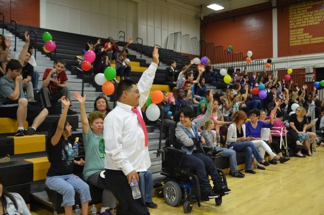 Calvin Sierra raises his hand high when asked if he knows what a hero is at a community hero-themed dance for special education students at Clark High School. (Ginger Meurer/Special to View)