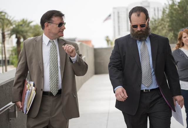 Attorney Chris Aaron, left, accompanies defendant Brian Jones, who is being sentenced in the HOA fraud scheme is seen outside the Lloyd George Federal Courthouse in Las Vegas on Wednesday, May 20, ...