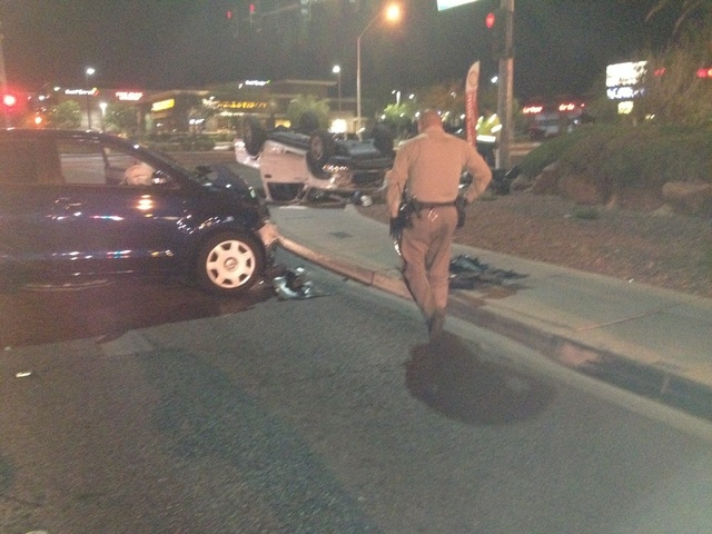 Las Vegas police are working at the scene of a two-car accident that left a Toyota pickup on its top at the intersection of Flamingo Road and Fort Apache Road on Monday night (Greg Haas/Las Vegas  ...