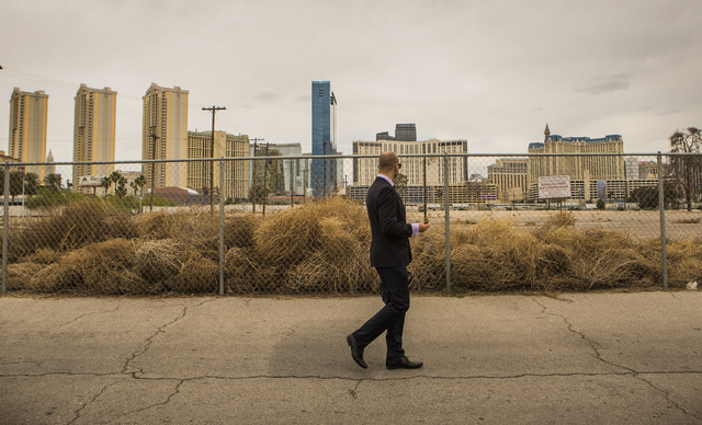 Jesse King walks passed a vacant lot at Harmon Avenue and Koval Lane on Thursday, May 14, 2015. A megaresort called Las Ramblas was planned on the site by actor George Clooney and Rande Gerber nea ...