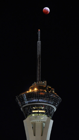 """A total lunar eclipse or """"blood moon"""" appears above the Stratosphere Tower on early Wednesday, Oct. 8, 2014, in Las Vegas. (David Becker/Las Vegas Review-Journal)"""