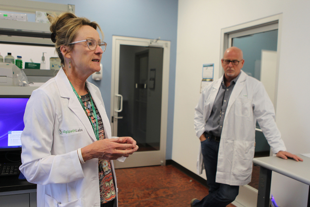DigiPath Labs employees Dr. Cindy Orser, left, chief science officer, with CEO Todd Denkin, give a tour of the DigiPath Labs facility in Las Vegas Wednesday, April 15, 2015. DigiPath Labs will be  ...