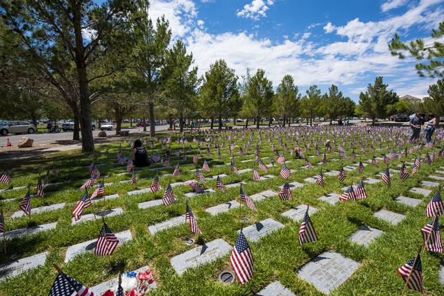Linda McKinnon, left, sits next to the grave site of her father, Glen, during the Memorial Day celebration at the Southern Nevada Veterans Memorial Cemetery in Boulder City, Nev. on Monday, May 25 ...