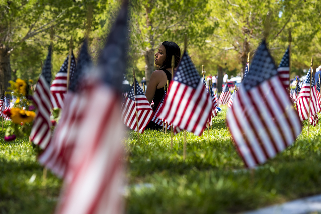 Linda McKinnon sits next to the grave site of her father, Glen, during the Memorial Day celebration at the Southern Nevada Veterans Memorial Cemetery in Boulder City, Nev. on Monday, May 25, 2015. ...