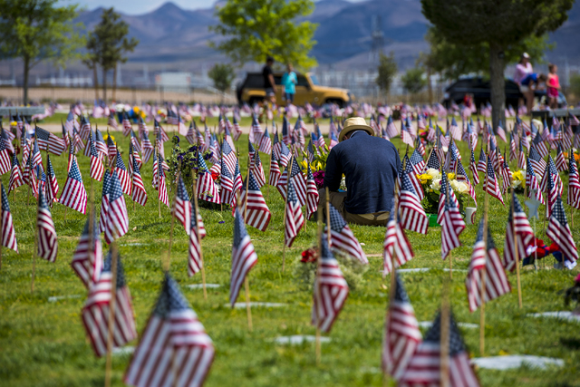 A man sits among American flags during the Memorial Day celebration at the Southern Nevada Veterans Memorial Cemetery in Boulder City, Nev. on Monday, May 25, 2015. (Joshua Dahl/Las Vegas Review-J ...