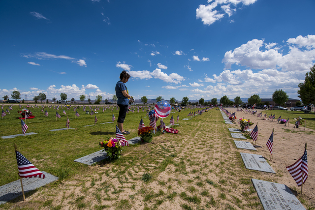 Kim Trodahl stands amongst flags during the Memorial Day celebration at the Southern Nevada Veterans Memorial Cemetery in Boulder City, Nev. on Monday, May 25, 2015. (Joshua Dahl/Las Vegas Review- ...