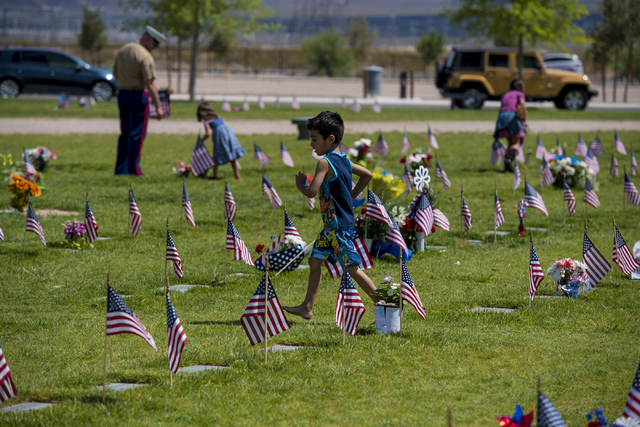 A young boy runs through the flags during the Memorial Day celebration at the Southern Nevada Veterans Memorial Cemetery in Boulder City, Nev. on Monday, May 25, 2015. (Joshua Dahl/Las Vegas Revie ...