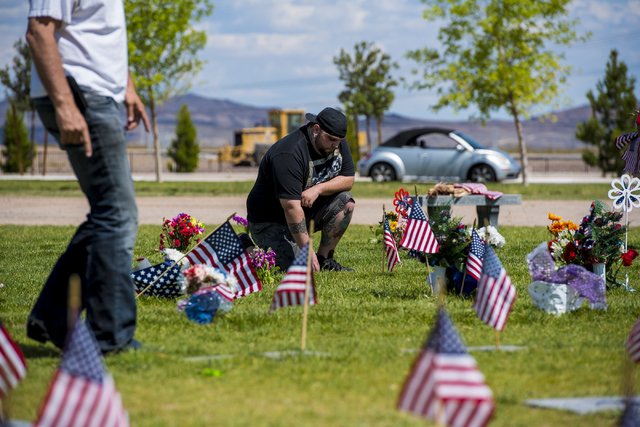 A man pays respects during the Memorial Day celebration at the Southern Nevada Veterans Memorial Cemetery in Boulder City, Nev. on Monday, May 25, 2015. (Joshua Dahl/Las Vegas Review-Journal)