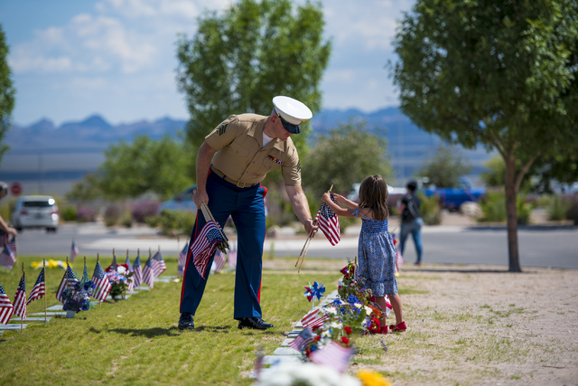 Marine Sgt Dane Haws and his daugher, Grace, help retrieve flags during the Memorial Day celebration at the Southern Nevada Veterans Memorial Cemetery in Boulder City, Nev. on Monday, May 25, 2015 ...