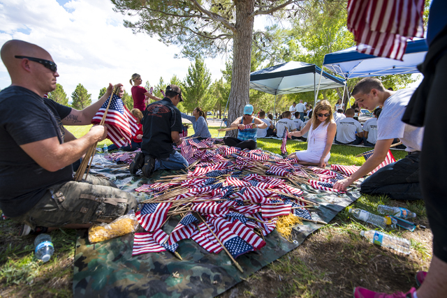 Volunteers help retrieve flags during the Memorial Day celebration at the Southern Nevada Veterans Memorial Cemetery in Boulder City, Nev. on Monday, May 25, 2015. (Joshua Dahl/Las Vegas Review-Jo ...