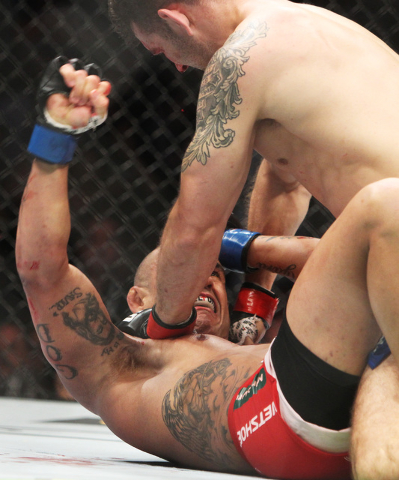 Chris Weidman rains punches down on Vitor Belfort on his way to a first round TKO during their middleweight title fight at UFC 187 Saturday, May 23, 2015, at the MGM Grand Garden Arena.  (Sam Morr ...
