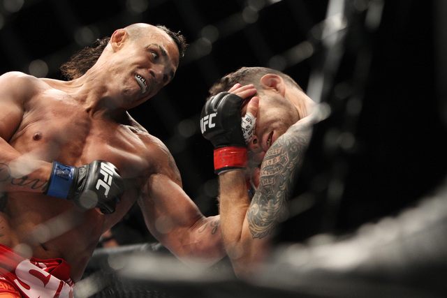 Chris Weidman gets hit with a left from Vitor Belfort during their middleweight title fight at UFC 187 Saturday, May 23, 2015, at the MGM Grand Garden Arena. Weidman retained his title with a firs ...