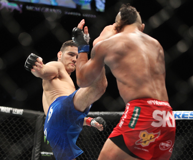 Chris Weidman lands a kick to the head of Vitor Belfort during their middleweight title fight at UFC 187 Saturday, May 23, 2015, at the MGM Grand Garden Arena. Weidman retained his title with a fi ...