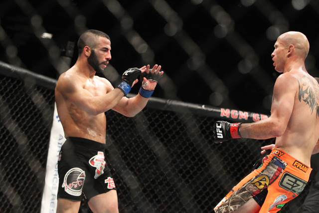 John Makdessi holds his hands up and backs away from Donald Cerrone after having his jaw broken during their fight at UFC 187 Saturday, May 23, 2015, at the MGM Grand Garden Arena. Cerrone won by  ...