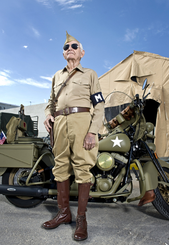 World War II veteran Gene Stephens, 94, wears his Military Police Corps uniform as he poses next to a vintage motorcycle at Battlefield Vegas, a military theme park on Industrial Road near Circus  ...