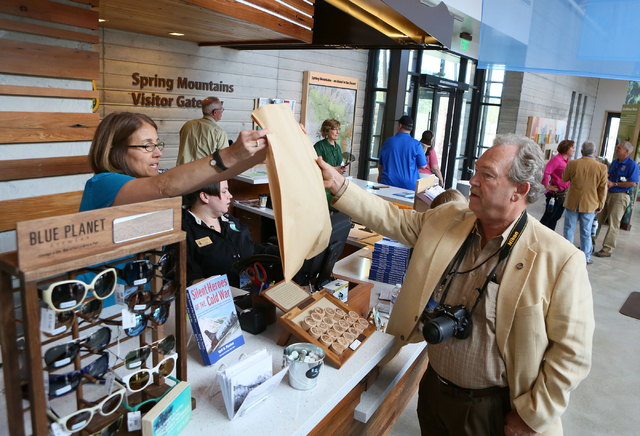 Connie Kane, left, hands a purchase to Dwight Mikel, right, in the gift shop at Spring Mountains Visitor Gateway Friday, May 30, 2015, in Kyle Canyon near Las Vegas. The new 128-acre complex is lo ...