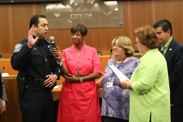 North Las Vegas Police Chief Alex Perez, left, is sworn in by city clerk Barbara Andolina, fourth from left, at a city council meeting at North Las Vegas City Hall on Wednesday, May 20, 2015. City ...