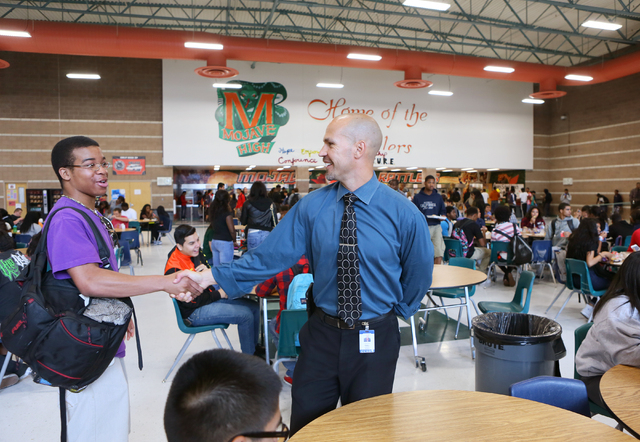Principal Antonio Rael, right, shakes hands and socializes with student Christsen Ellis, left, while supervising a lunch period at Mojave High School May 18, 2015, in North Las Vegas. (Ronda Churc ...