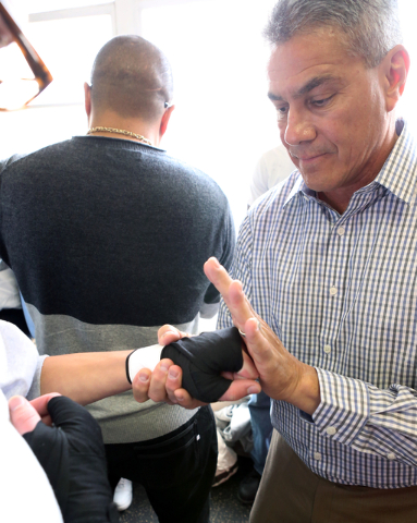 Referee Russell Mora inspects boxing hand wraps at the Spring Mountain Youth Camp Wednesday, April 22, 2015.  Professional boxers and boxing referees visited the camp, where young men ages 12 to 1 ...