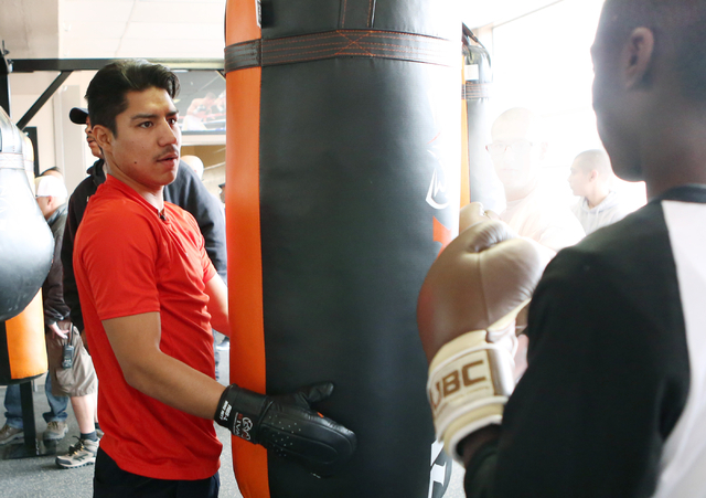 Boxer Jessie Vargas, left, gives a lesson on how to use a heavy punching bag to a young boxer at the Spring Mountain Youth Camp Wednesday, April 22, 2015.  Professional boxers and boxing referees  ...
