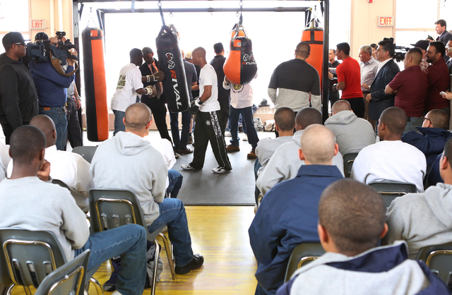 Youth watch as boxer Zab Judah, center, gives a lesson on how to use a heavy punching bag to a young boxer at the Spring Mountain Youth Camp Wednesday, April 22, 2015.  Professional boxers and box ...